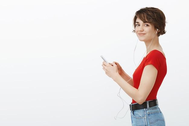 Profiel van :: knappe jonge vrouw kijken naar smartphone en luisteren muziek in koptelefoon, genieten van podcast