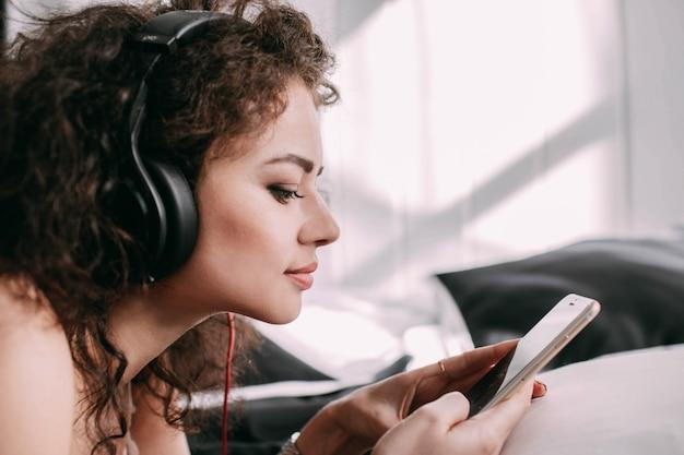 Profiel van krullende vrouw die naar de vrouw op bed luistert
