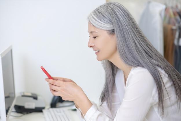 Profiel van :: lachende vrouw met lang grijs haar in witte blouse permanent achter toonbank kijken naar smartphone
