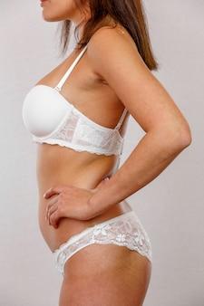 Profiel van mooi slank die vrouwenlichaam op grijs wordt geïsoleerd