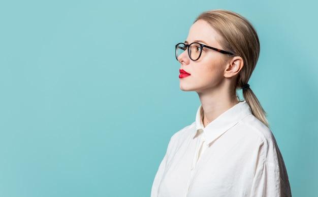 Profiel van mooie blonde in wit overhemd op blauwe muur