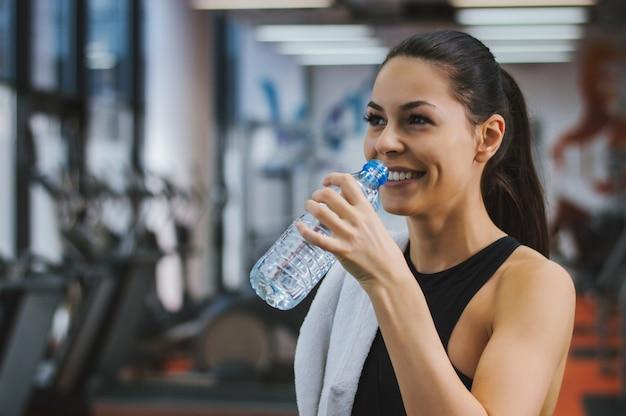 Profiel van mooie vrouw die wat water van plastic fles na training gaan drinken