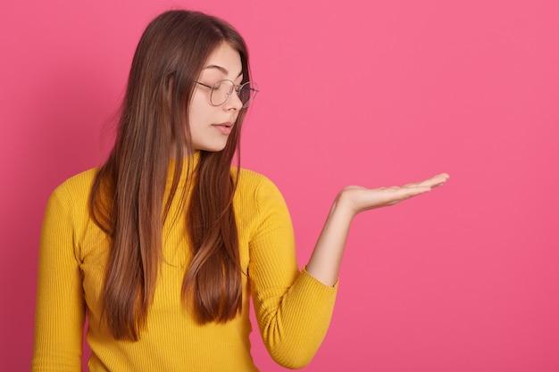 Profiel van nadenkend dromerig aantrekkelijk ernstig jong meisje dat opzij kijkt, één hand opheft, bril en geel sweatshirt draagt
