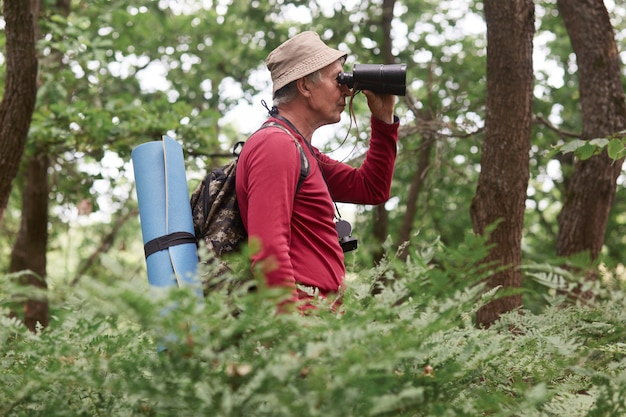 Profiel van oude reiziger die alleen gaat kamperen, omgeving controleert, door verrekijkers kijkt, dol op actieve levensstijl