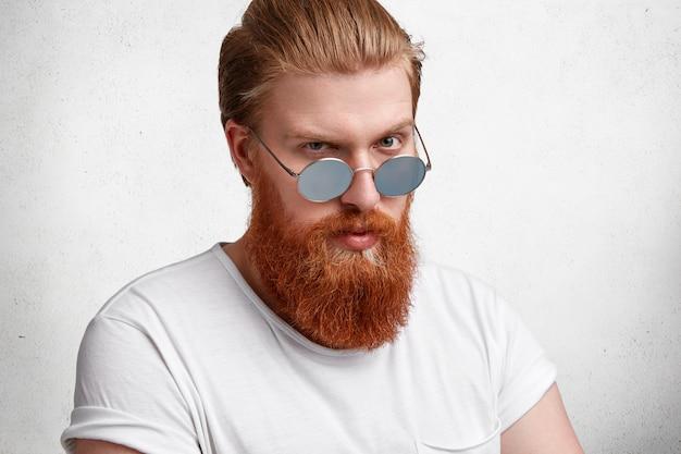 Profiel van :: strikte bebaarde man kijkt zelfverzekerd door zonnebril, heeft goed getrimde gember dikke baard en gezonde huid, gekleed in casual wit t-shirt