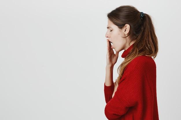 Profiel van uitgeputte vrouw geeuwen, deksel geopende mond met hand