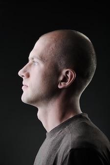 Profiel van witte kale man van in de twintig in het donker