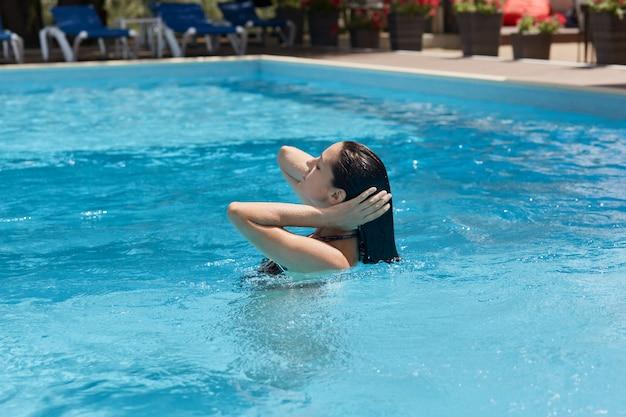 Profiel van :: zwartharige bevallige jonge vrouw zwemmen in het zwembad, tijd doorbrengen in luxe hotel spa resort