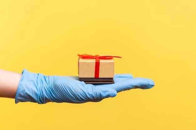 Profiel zijaanzicht close-up van menselijke hand in blauwe chirurgische handschoenen met kleine geschenkdoos.