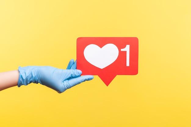Profiel zijaanzicht close-up van menselijke hand in blauwe chirurgische handschoenen met sociale media zoals stok.