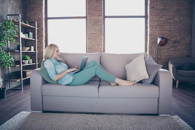 Profiel zijaanzicht portret van dame liggend op divan met behulp van laptop