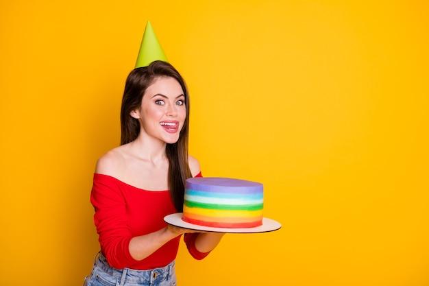 Profiel zijaanzicht portret van haar ze leuk aantrekkelijk grappig hongerig vrolijk meisje in handen lekker smakelijke taart likken lip kopie ruimte geïsoleerd helder levendig glans levendige gele kleur achtergrond
