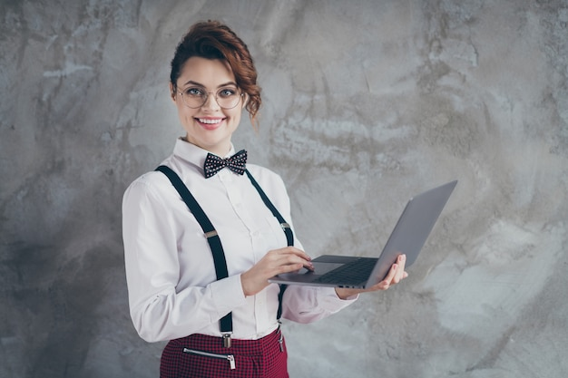 Profiel zijaanzicht portret van haar ze leuk aantrekkelijk mooi inhoud vrolijk vrolijk golvend meisje met behulp van laptop werken op afstand zelfontwikkelend geïsoleerd op grijze betonnen industriële muur achtergrond