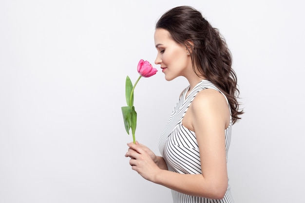 Profiel zijaanzicht portret van jonge brunette mooie vrouw met make-up in wit gestreepte jurk met tulp met gesloten ogen, ruikend en glimlachen. indoor studio opname, geïsoleerd op een grijze achtergrond.
