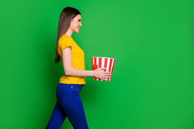 Profiel zijaanzicht portret van meisje dat in handen houdt met popcorndoos