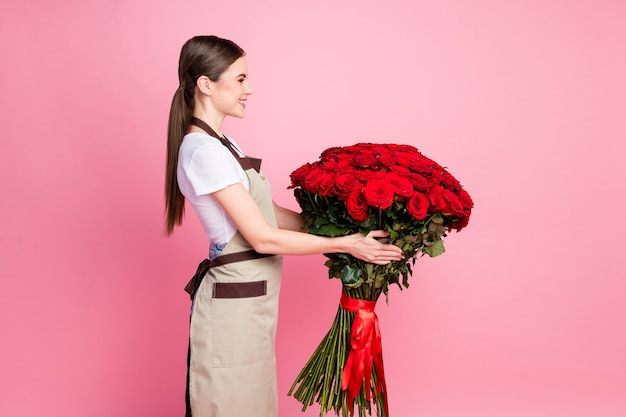 Profiel zijaanzicht portret van meisje met in handen grote rode rozen boeket