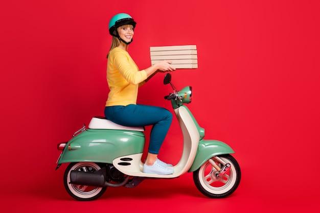 Profiel zijaanzicht portret van meisje rijden bromfiets dragende stapel pizza op rode muur