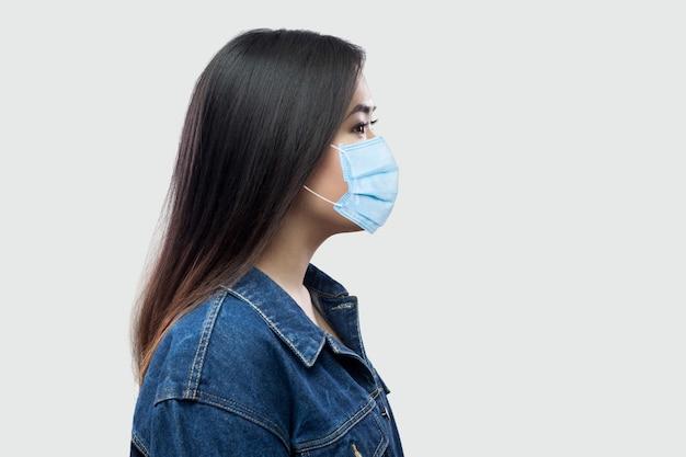 Profiel zijaanzicht portret van rustige serieuze mooie brunette aziatische jonge vrouw met chirurgisch medisch masker in blauwe jas staan en kijken. indoor studio opname, geïsoleerd op lichtgrijze achtergrond.
