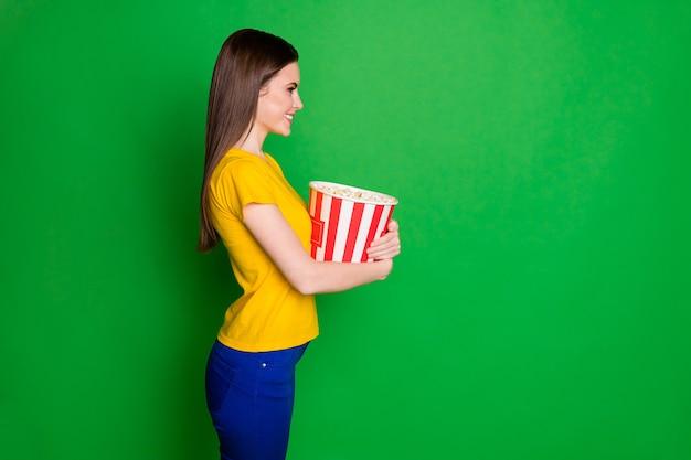Profiel zijaanzicht portret van vrolijk, steil meisje dat in handen grote maïsdoos houdt