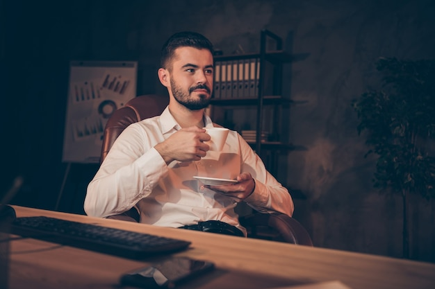 Profiel zijaanzicht van dromerige man zitten leunstoel tafel houden koffie drinken