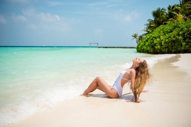 Profiel zijaanzicht van haar, ze is aardig, mooi, sierlijk, dun langharig meisjesmodel, zittend op plage, genietend van de beste zonnige warme dag, goed weer, zonnebaden aan zee