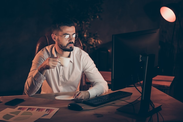 Profiel zijaanzicht van man zitten tafel bureau werken op pc computer koffie drinken