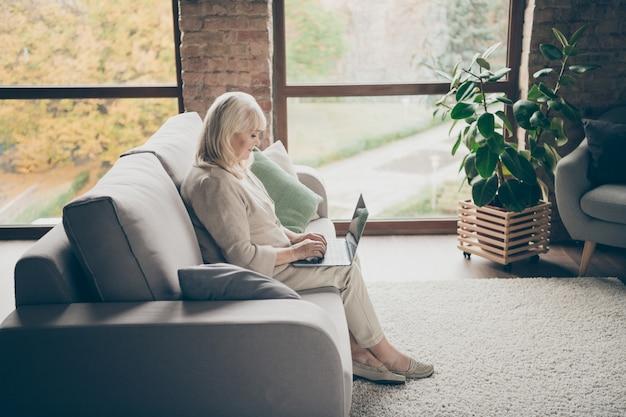 Profiel zijaanzicht van mooie aantrekkelijke vreedzame gerichte grijsharige dame zittend op een divan schrijven e-mail browsen informatie online arts overleg industriële baksteen loft moderne stijl interieur huis