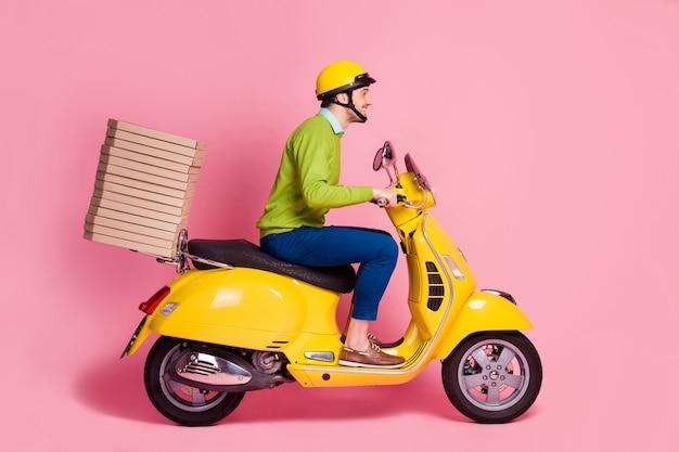 Profiel zijaanzicht van vrolijke kerel rijden bromfiets stapel pizza brengen