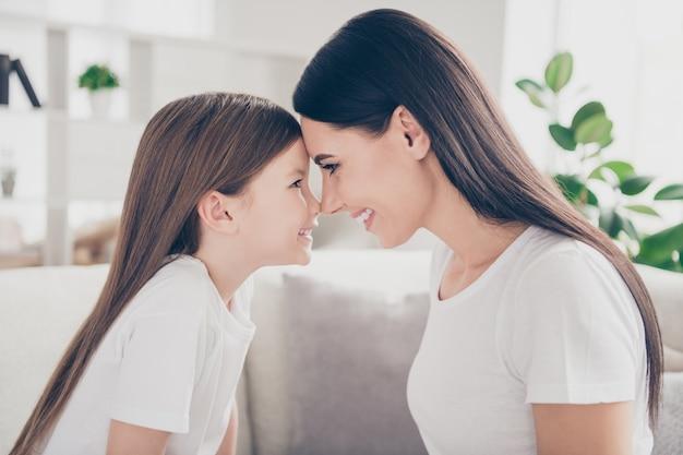 Profiel zijfoto van moeder dochter voorhoofd elkaar in kamer appartement