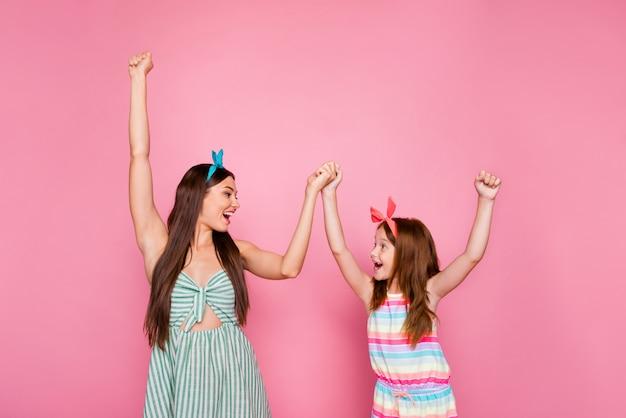 Profiel zijfoto van opgewonden twee mensen hand in hand schreeuwend met heldere jurk rok hoofdbanden geïsoleerd op roze achtergrond