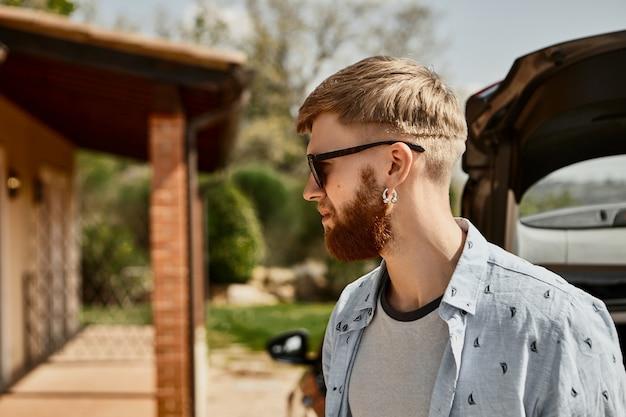 Profielafbeelding van modieuze jonge hipster man met trendy kapsel en dikke gemberbaard