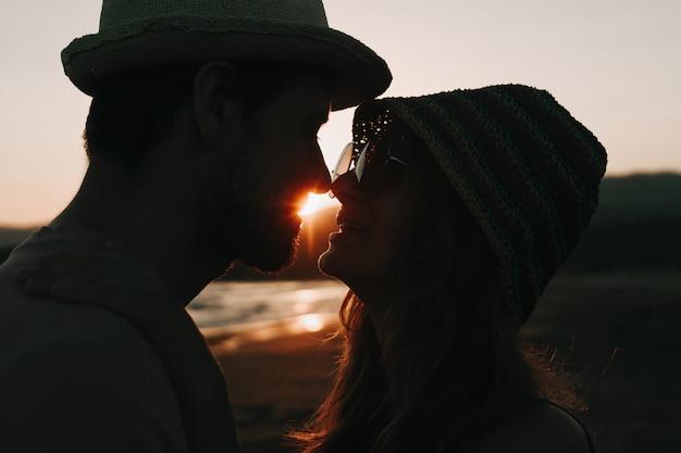 Profielen van romantisch paar die elkaar op achtergrond van zonsondergangstrand bekijken.