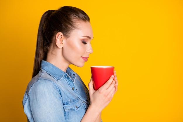 Profielfoto aan de zijkant van een kalm, vredig meisje, houd een latte-beker vast, geniet van de geur, het aroma, draag mooie kleding die is geïsoleerd over een glanzende kleurachtergrond
