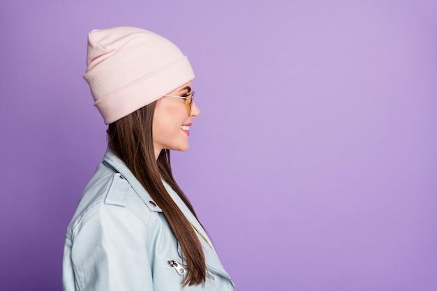 Profielfoto aan de zijkant van een leuk lief schattig jong meisje valt vrije tijd vakantie kijk copyspace luister vrienden dragen casual stijl kleding geïsoleerd over violet gekleurde achtergrond