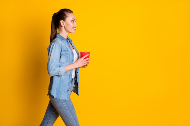 Profielfoto aan de zijkant van een mooi openhartig meisje, ga lopen copyspace, houd latte cup vast, geniet van vrije tijd, draag een casual stijl outfit geïsoleerd op een felle kleur achtergrond