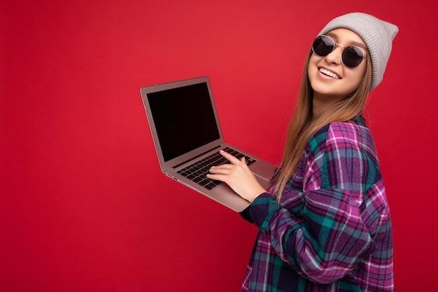 Profielfoto aan de zijkant van een mooie glimlachende, gelukkige jonge vrouw die een computer vasthoudt met een casual smart
