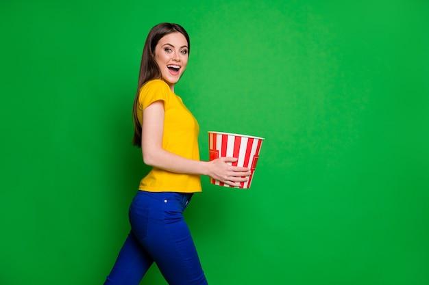 Profielfoto aan de zijkant van een positief meisje houdt een grote popcorndooswandeling vast