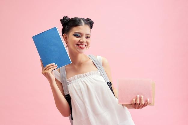 Profielfoto aan de zijkant van een positief meisje houdt kopieerboeken vast, ga lopen klaslokaal les college bibliotheek geïsoleerd over roze achtergrond