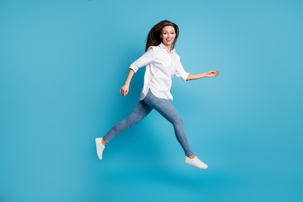 Profielfoto op volledige grootte van aantrekkelijke dame die hoog springt en een wit overhemd jeans schoenen draagt, geïsoleerde blauwe achtergrondkleur