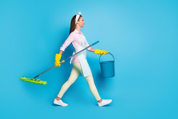 Profielfoto op volledige grootte van een positieve professionele schoonmaakster, meisje met dweil emmer lopen