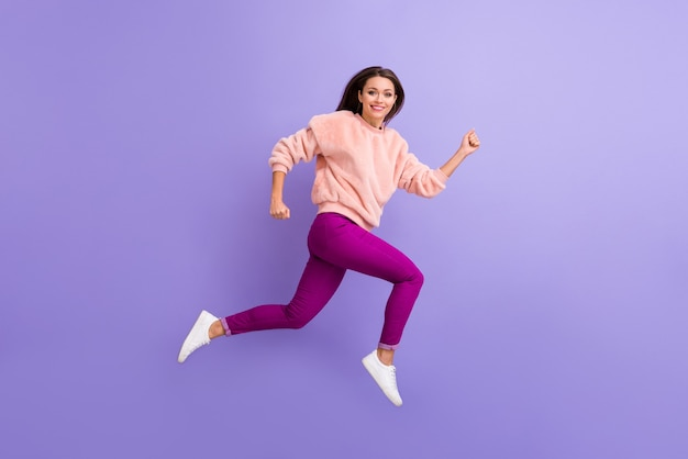 Profielfoto op ware grootte van een dame die hoog springt en vrijetijdskleding draagt op een paarse muur