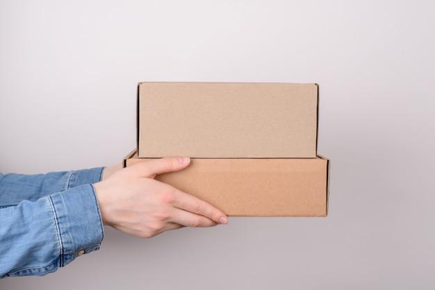 Profielfoto van armen met twee kartonnen dozen