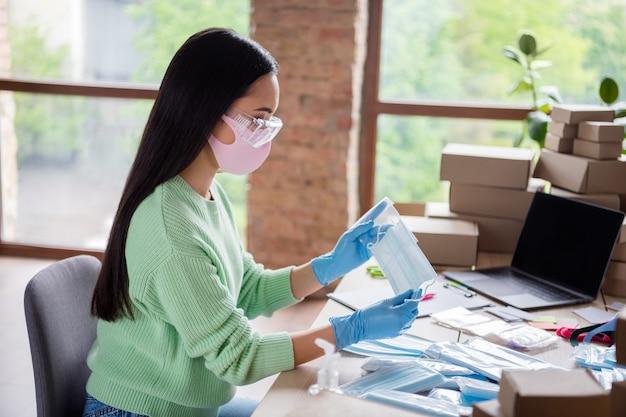 Profielfoto van aziatische dame familiebedrijf orde bestelling gezichtsgriep medisch masker verzenden voorbereiden levering controleren antivirale veiligheid ademhalingstoestellen in ritszak blijven thuiskantoor binnenshuis