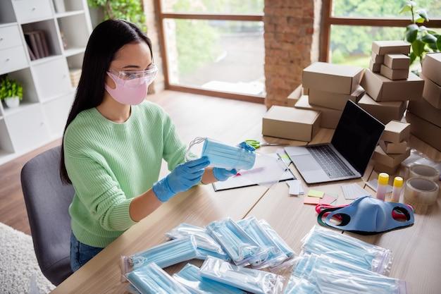 Profielfoto van aziatische dame familiebedrijf orde gezichtsgriep medisch masker verzenden voorbereiden levering anti-virale veiligheid plaats ademhalingstoestellen in ritszak blijf thuiskantoor binnenshuis