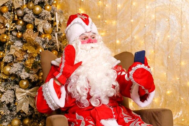 Profielfoto van bebaarde kerstman met smartphone maakte indruk op kersttraditie van het seizoen van...