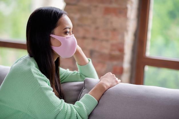 Profielfoto van behoorlijk trieste corona-virus zieke patiënt aziatische chinese dame zit gezellig op de bank kijk dromerig raam ontbreekt naar buiten gaan moet zelfisolatie houden sociale afstand blijf binnen thuis