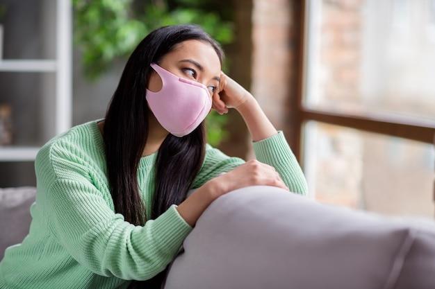 Profielfoto van behoorlijk trieste corona-virus zieke patiënt huiselijke aziatische dame zit zachte gezellige bank kijk dromerig raam ontbreekt naar buiten gaan moet zichzelf isoleren blijf binnen thuis