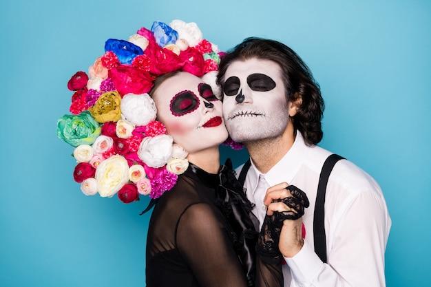 Profielfoto van charmant griezelig romantisch koppel man dame hand in hand ontmoeten elkaar na levenslang afscheid dragen zwarte jurk dood kostuum rozen hoofdband bretels geïsoleerde blauwe kleur achtergrond