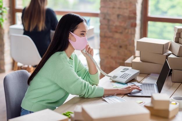 Profielfoto van chinese zakenvrouw manager organiseren medische gezichtsmaskers bestellingen leveringsdozen spreken vaste lijn klantdetails noteren van informatie notebook thuiskantoor binnenshuis