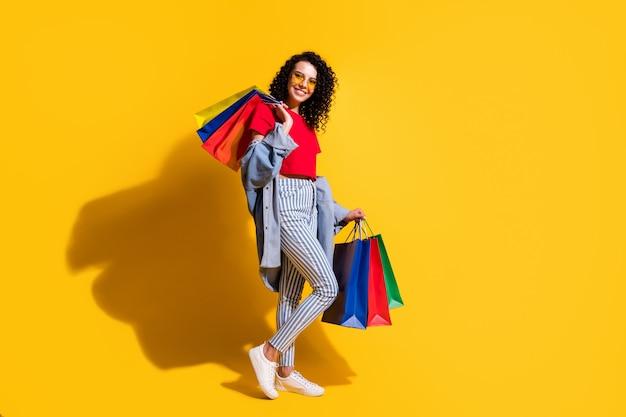 Profielfoto van dame kijkt camera houdt winkelpakketten draag rood t-shirt gestreepte jeans jas zonnebril sneakers geïsoleerde gele kleur achtergrond